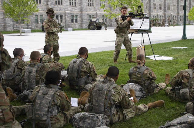 Pfc. Justin Garrison, from 2nd Battalion, 2nd Infantry Regiment, 3rd Brigade, 10th Mountain Division, shows the immediate action needed during a rifle malfunction to the new cadets July 23 on The Plain. Drill sergeant Sgt. Darren O'Dell oversees the training of the new cadets.