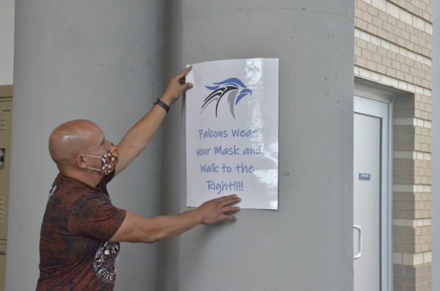 Alberto Gonzalez, security specialist for Fort Campbell High School, hangs posters, Aug. 18, reminding students and staff to social distance in preparation for Aug. 24, the first day of school. (Emily Laforme, Fort Campbell Courier)