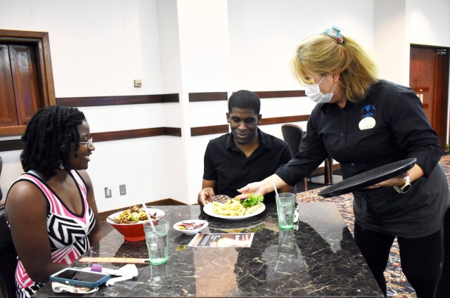 Lamario Harris, center, and his wife Tiara, left, eat dinner at the Camp Zama Community Club, Camp Zama, Japan, Aug. 20, after attending a Money Matters Virtual Marriage Workshop hosted by the Camp Zama Religious Support Office. The free dinner was part of the workshop.