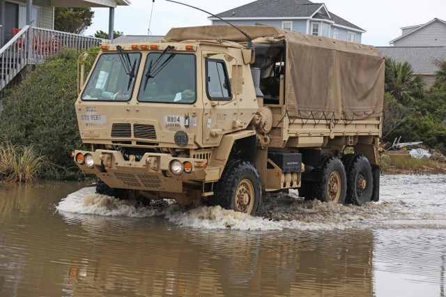 Vehicles assigned to the 878th Engineer Vertical Construction Company, 105th Engineer Battalion, drive through flooded roads and debris on the way to assist stranded civilians on Oak Island, N.C., Aug. 5, 2020. The North Carolina National Guard deployed teams across the Eastern portion of the state to assist civilians and North Carolina Emergency Management with damage inflicted by Hurricane Isaias.