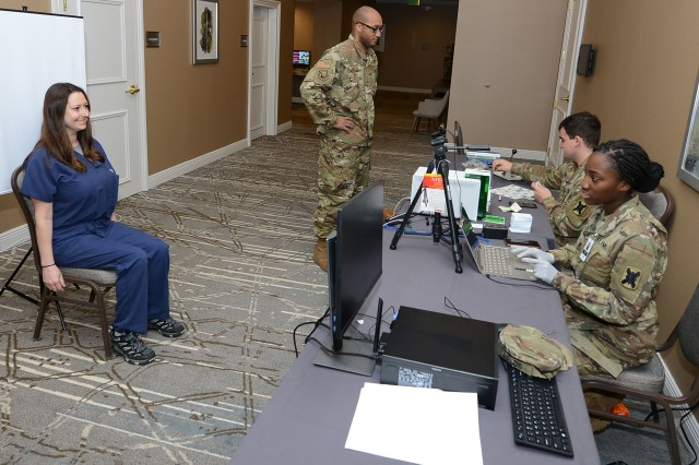 Spc. Shunterika Fields and Army Pvt. Stephen Hines create ID cards to track non-patient personnel's temperatures at the temporary medical facility in New Orleans, April 4. U.S. Northern Command, through U.S. Army North, is providing military support to the Federal Emergency Management Agency to help communities in need.