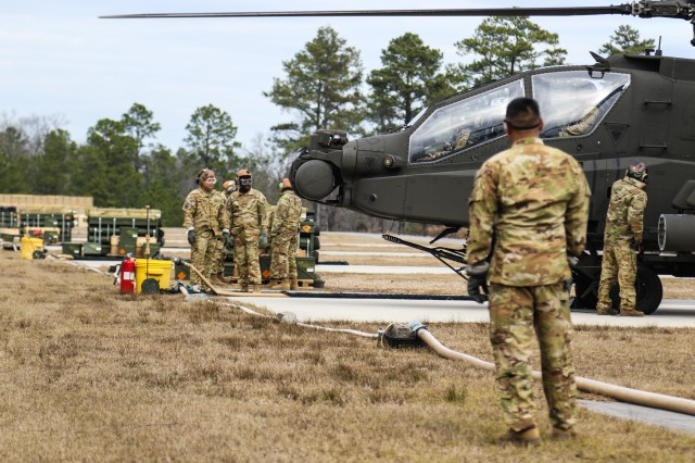 Soldiers assigned to 1st Attack Reconnaissance Battalion, 82nd Combat Aviation Brigade, prepare ammunition and fuel for a U.S. Army AH-64D Apache Longbow during an aerial gunnery range exercise at Fort Bragg, North Carolina, Jan. 27, 2020. The exercise allowed pilots to perform qualifications on the Apache's weapons system and maintain mission readiness. (U.S. Army photo by Pfc. Joshua Cowden, 22nd Mobile Public Affairs Detachment)