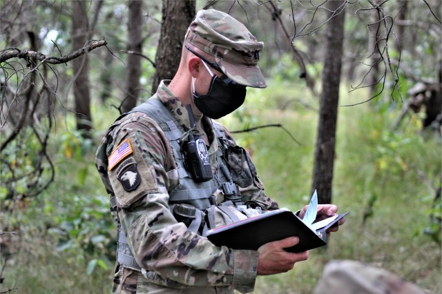 Capt. Terry Battison, a professor of military science at the Marquette University ROTC program, checks his notebook while leading field training Aug. 6, 2020, on a training area at Fort McCoy, Wis. Dozens of ROTC cadets from seven universities trained at Fort McCoy for 10 days in early August in a special training exercise that was created because of the loss of previous training opportunities for cadets because of the COVID-19 pandemic. (U.S. Army Photo by Scott T. Sturkol, Public Affairs Office, Fort McCoy, Wis.)