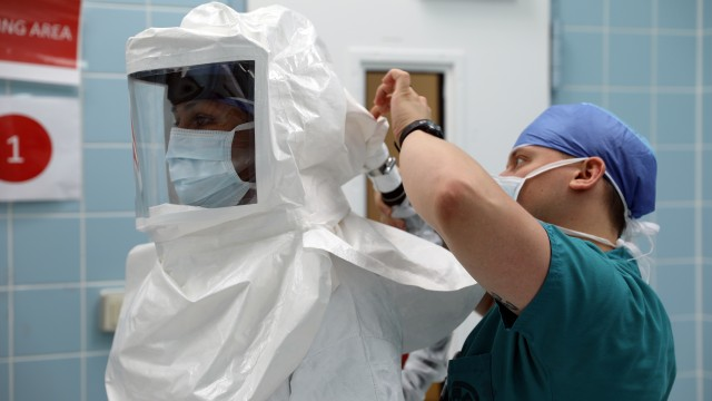 Maj. (Dr.) Neel Shah, an anesthesiologist at Landstuhl Regional Medical Center, gets assistance with putting on a powered air-purifying respirator.