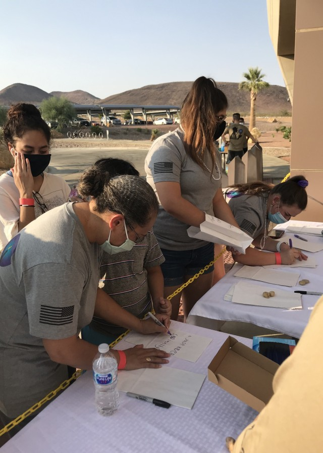 Soldiers, civilians and community members write words of encouragements of paper bags before Weed Army Community Hospital's Suicide Prevention Awareness Walk Sept. 1 at Fort Irwin, Calif. (U.S. Army photo by Lt. Col. Jacquelin Coleman-Adams, WACH)