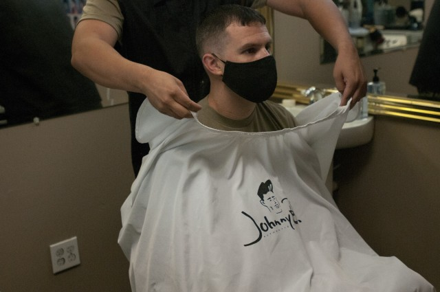 U.S. Army Reserve Sgt. Bryan Herrera lifts off his customer's barber sheet after completing a haircut at Lilian's Beauty Salon and Barbershop in Richmond, Virginia Aug. 18, 2020. Herrera balances a career as an Army Reserve NCO along with a full-time career as a barber and business owner.  (U.S. Army Reserve photo by Spc. Eric Zedalis)