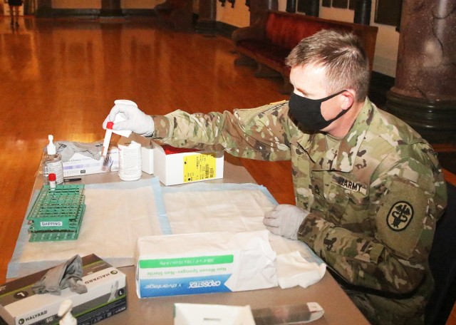 Sgt. 1st Class Eric Holman, senior clinical nurse NCOIC at Keller Army Community Hospital, places the viral transport media (test tube) into a container that is then transported to KACH for COVID-19 testing.