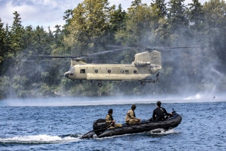 A Green Beret Soldier helocasts into a lake from a CH-47 Chinook helicopter at Joint Base Lewis-McChord, Wash., June 30, 2020.