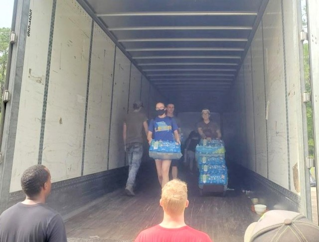 From left: Sgt Hannah Johnson, Spc. Claudia Herrera and Pvt. 1st Class Kevin Truska, volunteers from the 204th Military Police Company, 519th Military Police Battalion, help offload supplies at the Beauregard Parish central donation center.