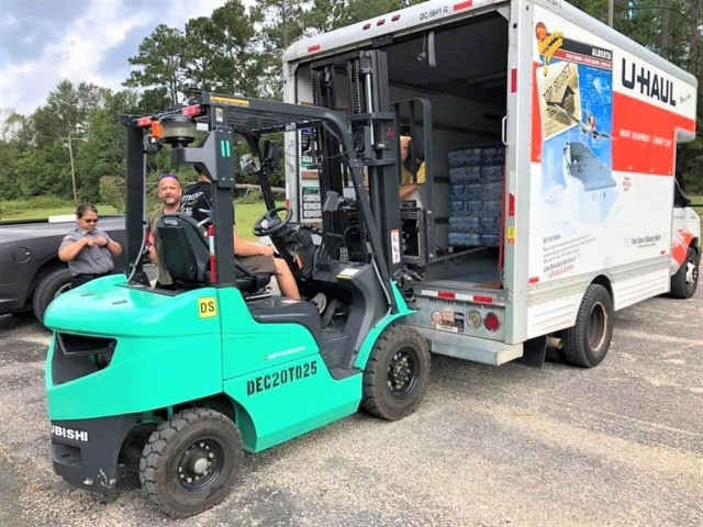 Spc. Juan Martinez, forklift operator and volunteer from 41st Transportation Company, 519th Military Police Battalion, offloads donated palettes of water at the Beauregard Parish centralized donation point in the wake of Hurricane Laura.