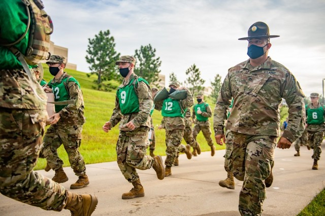 """Trainees undergoing Infantry One-Station Unit Training here haul supplies on the run in August 2020 during their first day of training. The mock battlefield resupply exercise is part of The First 100 Yards, developed by the U.S. Army Infantry School at Fort Benning as a constructive way to start instilling the Infantry warrior ethos and other basic Soldier habits from the first day. It replaces the traditional """"shark attack"""" known to generations of Soldiers, in which drill sergeants would swarm new recruits and shout orders and criticism as a way to achieve psychological dominance. The First 100 Yards is explained in a video by the Infantry School's senior enlisted leader, Command Sgt. Maj. Robert K. Fortenberry, and was one of several warfighting-related videos available for viewing during the recent 2020 Virtual Maneuver Warfighter Conference, which was held online by Fort Benning's U.S. Army Maneuver Center of Excellence, of which the Infantry School is a part."""