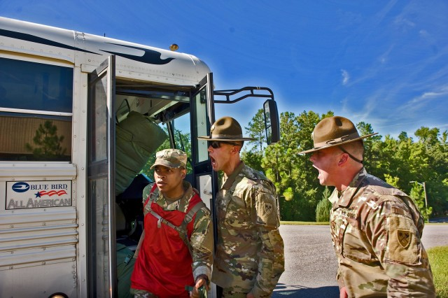 """In an August 2016 photo, new recruits arriving for basic training here encounter the traditional """"shark attack"""" in which drill sergeants bark orders and other comments to establish psychological dominance and impress upon the new arrivals the need for proper compliance to orders.  But the U.S. Army Infantry School at Fort Benning has ended the shark attack, which dates to a period when many in the Army's ranks were draftees, in favor of a more constructive way of transitioning today's generations of Infantry volunteers into their initial training. It's called The First 100 Yards, and is explained in a video by the Infantry School's senior enlisted leader, Command Sgt. Maj. Robert K. Fortenberry. The video was one of several warfighting-related videos available for viewing during the recent 2020 Virtual Maneuver Warfighter Conference, which was held online by Fort Benning's U.S. Army Maneuver Center of Excellence, of which the Infantry School is a part."""