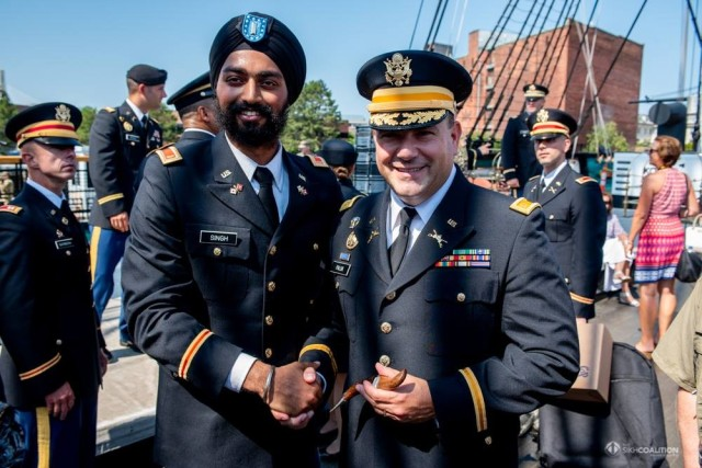 """Second Lt. Kanwar Singh, left, presents his """"kirpan"""" or Sikh dagger to officer candidate school commander, Maj. Christian Paluk of the 101st Regiment, Regional Training Institute following Singh's commissioning ceremony in Boston."""