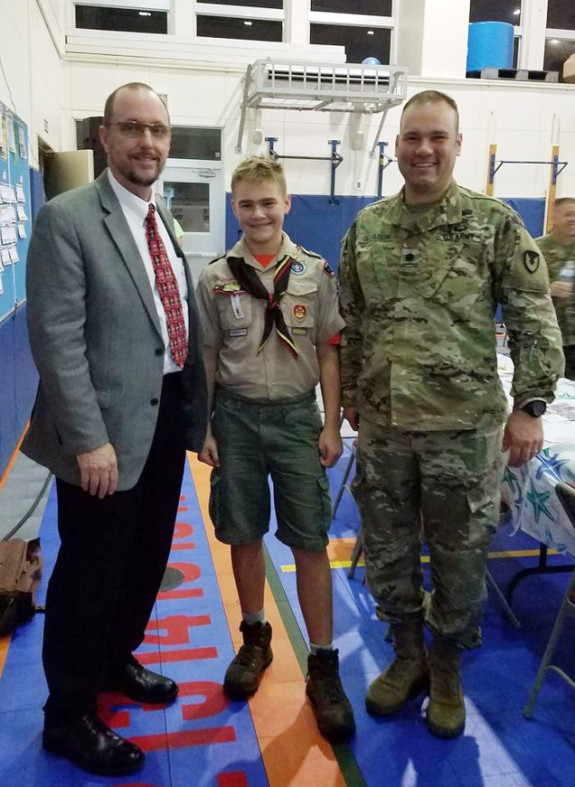 Lt. Col. Joel Gleason, commander of U.S. Army Garrison Okinawa and Scoutmaster of Boy Scout Troop 101 in Okinawa; his son Colton; and Jim Journey, superintendent of the Department of Defense Educational Activity Pacific South District, pose for a photo in Okinawa, Japan, after an Okinawa District Advisory Committee in March. For Colton to earn the Citizenship in the Community Merit Badge, he had to attend a community meeting where participants debated ideas, and the committee meeting met the requirement.