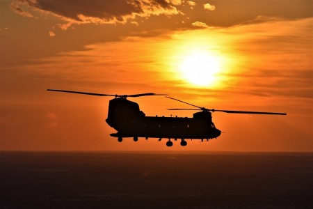 The sunset is visible behind a CH-47 Chinook helicopter as it flies over Fort Hood, Texas, Aug. 2, 2020.