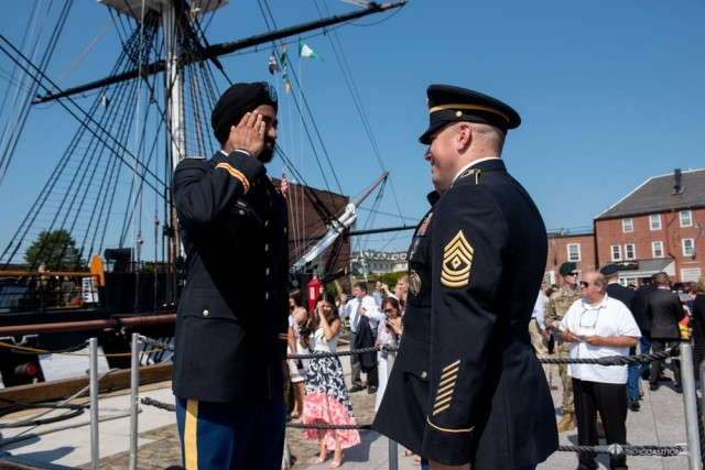 Kanwar Singh renders his first salute to his former recruiter, 1st Sgt. John Helbert, during his commissioning ceremony in Boston.