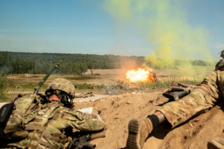 Paratroopers take cover as a bangalore torpedo explodes, taking out a mined wire obstacle during a combined arms live fire training range in the Grafenwoehr Training Area, July 29, 2020.