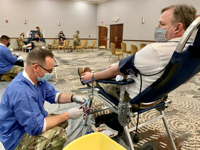 Sgt. Brett Knox with the Kendrick Memorial Blood Center, located outside Fort Gordon, takes blood from Patrick Young, an employee at Winn Army Community Hospital, as a participant in the DoD COVID-19 Convalescent Plasma Program, Sept. 3.  (Photo by Zach Rehnstrom)