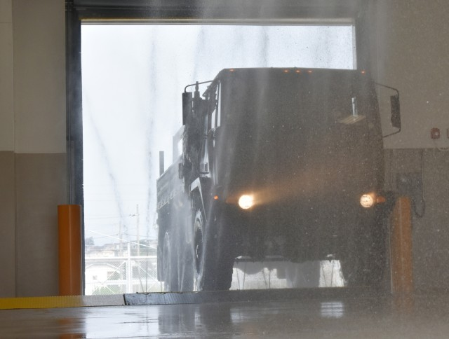 Spc. Eeralle Jones, assigned to the 38th Air Defense Artillery Brigade, drives a truck over the undercarriage cleaning system at the U.S. Army Garrison Japan Wash Rack at Sagami General Depot, Japan, Sept. 21.