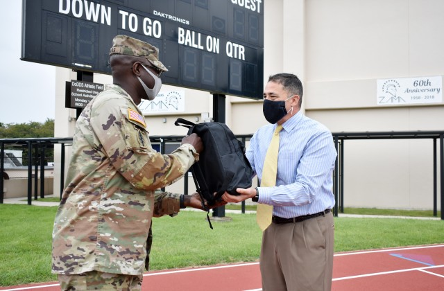 Lt. Col. Demetrick Thomas, left, commander of the 35th Combat Sustainment Support Battalion, hands Henry LeFebre, principal of Zama Middle High School, a backpack full of school supplies at the school, Camp Zama, Japan, Sept. 24. The battalion has an Adopt-A-School Program agreement to sponsor the school.