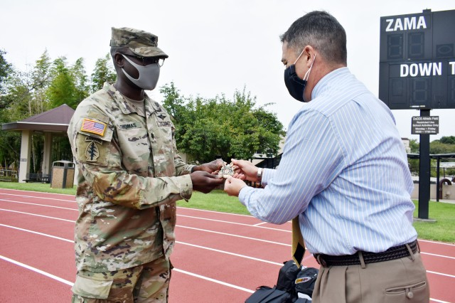 Lt. Col. Demetrick Thomas, left, commander of the 35th Combat Sustainment Support Battalion, presents Henry LeFebre, principal of Zama Middle High School, a battalion coin at the school, Camp Zama, Japan, Sept. 24. The battalion has an Adopt-A-School Program agreement to sponsor the school.