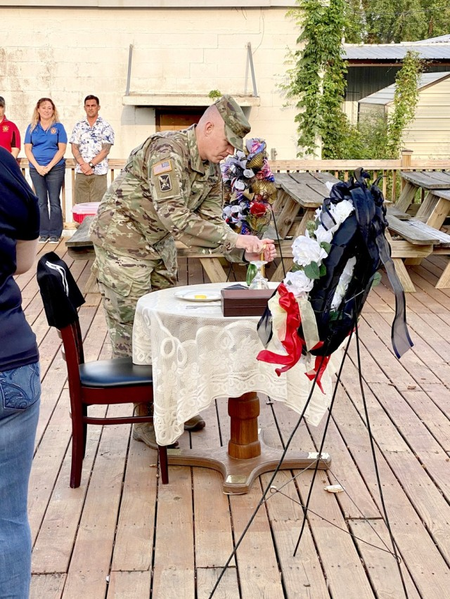 Col. Ryan K. Roseberry, Fort Polk Garrison Commander lights the candle on the missing man table during the Leesville POW/MIA Remembrance Ceremony on Sep. 18.  The flame represents the unconquered spirit of prisoners of war.