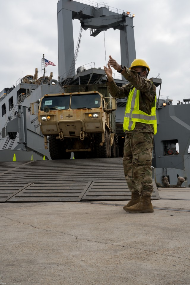 U.S. Army Pvt. Martavius Douglas, a Cargo Specialist (88H) with 368th Seaport Operations Company, 11th Transportation Battalion, 7th Transportation Brigade (Expeditionary), directs a vehicle off the U.S. Naval Ship, Fisher, in Port Arthur, Texas, Sept. 25, 2020.  The Joint Readiness Exercise allows the U.S. Army to assess the unit's alert and recall procedures, pre-deployment processes and transportation of personnel and equipment.   (U.S. Army photo by Sgt. Marygian Barnes, 22nd Mobile Public Affairs Detachment)