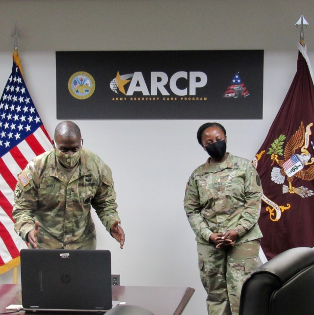 Army Surgeon General Lt. Gen. R. Scott Dingle (left) spoke to Master Sgt. Starrenzo Cummings virtually during a recognition ceremony that he attended from a temporary duty location. Cummings and Maj. Jemah Parker (right) were recognized for assisting with COVID-19 operations while still performing their duties for the Army Recovery Care Program. Upon his return, Cummings will receive an Army Surgeon General coin. (U.S. Army photo courtesy of Julia Oliveri)