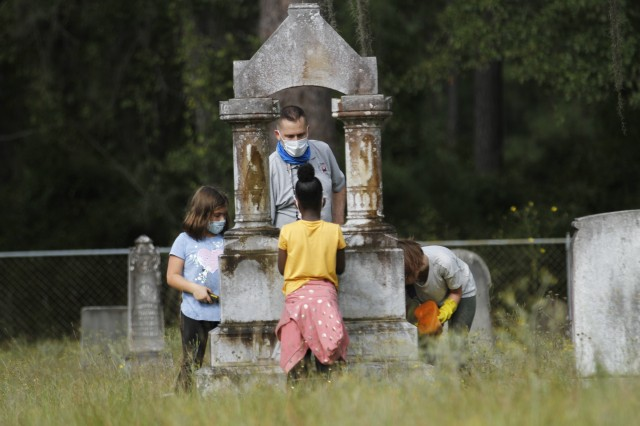 Brian Greer, an archaeologist with Directorate of Public Works, Environmental Division, Prevention and Compliance Branch, Cultural Resource Management, and children of Fort Stewart schools work to clean headstones Sept. 25 at Taylors Creek Cemetery on Fort Stewart in honor of National Public Lands Day. The children and volunteers helped clean up half of the nearly 450 headstones in the cemetery in July, and continued to perform maintenance on the rest when they returned this day.