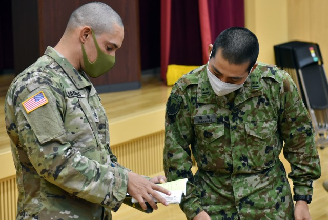 Staff Sgt. James Hankins, left, individual mobilization augmentee manager for U.S. Army Reserve Affairs Japan, U.S. Army Japan, speaks with 1st Lt. Akito Saruge, a member of the Japan Ground Self-Defense Force, during an exercise included in the JGSDF Reserve Interpreters Training symposium at Camp Zama, Japan, Sept. 24.