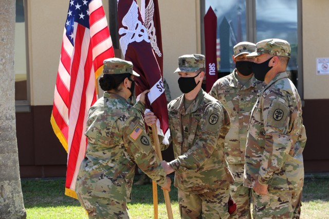 After receiving the new Soldier Recovery Unit's colors from Col. Martin Doperak, Tripler Army Medical Center commander, Lt. Col. Marie F. Slack, passes the colors to Command Sgt. Maj. Christian G. Davis.