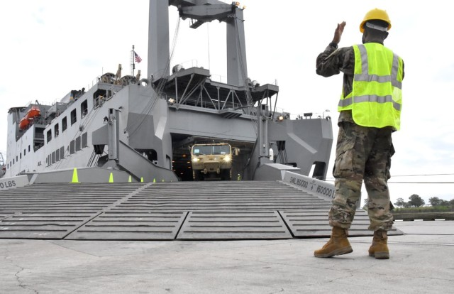 A Soldier with 7th Transportation Brigade gives hand signals to a Soldier offloading a vehicle at Port Arthur, Texas, Sept. 25 as part of Joint Readiness Exercise 20. The vehicle will be used by the 2nd BCT, 25th Inf Div during JRTC Rotation 21-01.