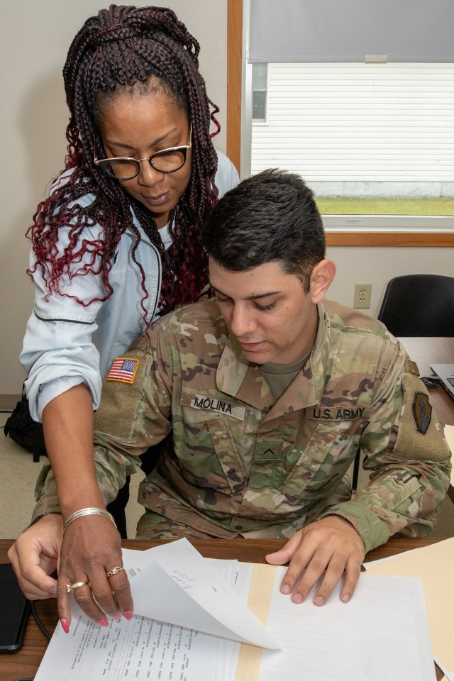 Johnjulyn Newman, Defense Finance and Accounting Service Defense Military Pay Office military pay technician, points out additional information to U.S. Army Pvt. Josue Molina, financial management technician, during Diamond Saber 2019 at Fort McCoy, Wis., June 28, 2019. DFAS brought realism to the Army's largest financial management exercise through live coding of actual Soldier's pay. (U.S. Army photo by Mark R. W. Orders-Woempner)