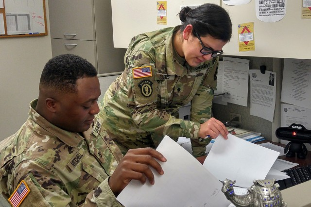 In this archive photo, Pfc. Detron R. Mitchell, left, and Spc. Iris I. Claros, right, consolidate documents in the disbursing section of the Defense Military Pay Office for an inspection by the Network Audit Field Compliance Division of the Defense Finance and Accounting Service at Fort Campbell, Ky. Feb. 20, 2017. The U.S. Army Financial Management Command assumed the Army's military pay mission from the Defense Finance and Accounting Service on Oct. 1, 2020. (U.S. Army photo by 1st Lt. Todd A. Kuzma)