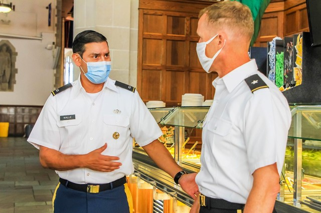 Chief Warrant Officer 4 Edgar Walle, the installation food advisor (left), explains the healthier options for cadets in the new menu to Brig. Gen. Curtis Buzzard, Commandant of Cadets. Through the Go For Green program, Walle changed the entire menu to implement healthier food options and discard all fried foods.