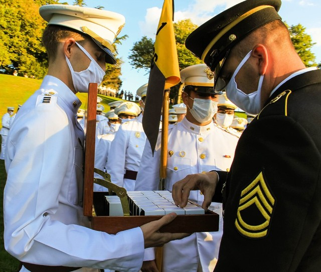 A brigade tactical noncommissioned officer starts to distribute the rings to the Class of 2021 at the Ring Ceremony.