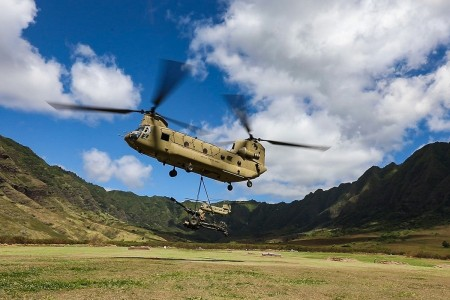 A CH-47 Chinook Helicopter from the 25th Combat Aviation Brigade, 25th Infantry Division, carries an M119A3 Howitzer from Schofield Barracks, Hawaii to Makua Valley, Hawaii during a joint field artillery exercise, Aug. 11, 2020.
