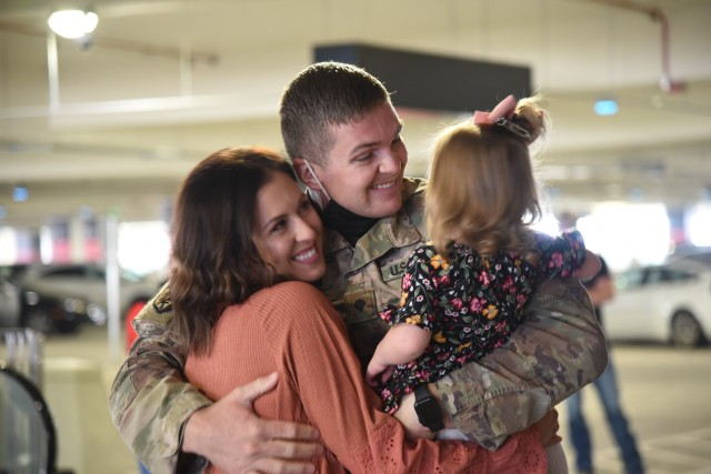 Spc. Luke Morgan, assigned to the 1st Attack Reconnaissance Battalion, 211th Aviation Regiment, greets his family at the Salt Lake City International Airport, Utah, Oct. 6, 2020.