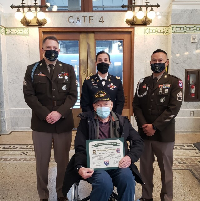 (l to r) Army Sgt. Jake H. Johnson, Capt. Paula Heap and Staff Sgt. Vetoun Khy, with the Seattle Army Recruiting Battalion, honor WWII veteran Army Cpl. James Edward Reed with a Certificate of Appreciation, an eagle statue, and a battalion coin, during Reed's one-day round-trip train ride aboard the Empire Builder, Oct. 15, 2020, from St. Paul/Minneapolis to Seattle.