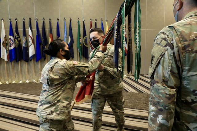 KADENA AIR FORCE BASE, Japan – Lt. Col. Rosanna Clemente, 1st Battalion, 1st Air Defense Artillery Regiment commander, passes the battalion colors to Command Sgt. Maj. Daniel S. Venton, signifying the transfer of responsibility during an assumption of responsibility ceremony at the Rocker Enlisted Club here Oct. 20. Venton took over as the new senior enlisted advisor of the Snake Eyes Battalion.