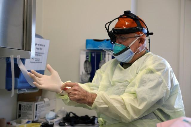 Col. (Dr.) Tom Goksel, an oral maxillofacial surgeon, prepares for surgery.
