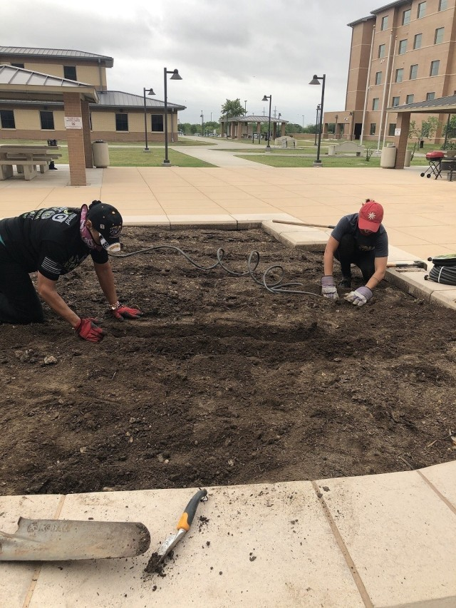 Master Sgt. Mary Jackson and former Joint Base San Antonio-Fort Sam Houston Soldier Recovery Unit Recreational Therapist Kersey Henderson work in the new garden at Liberty Barracks. (U.S. Army photo courtesy of Angel Flores)
