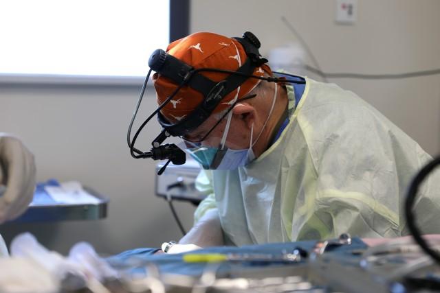 Col. (Dr.) Tom Goksel, an oral maxillofacial surgeon, removes molar teeth from a service member.