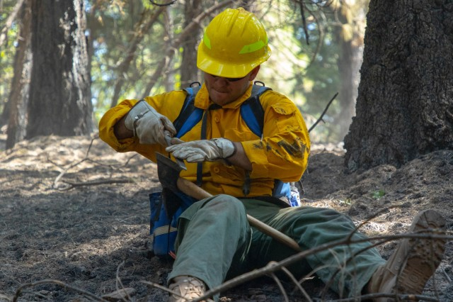 Spc. Bailey Walker with the 14th Brigade Engineer Battalion, from Joint Base Lewis-McChord, Washington, sharpens his Pulaski after mopup operations in Mendocino National Forest, Nothern California, Friday, Sept. 4, 2020. The Pulaski, a special hand tool used in fighting wildfires, combines an axe and an adze in one head and is used for constructing firebreaks, dig soil and chop trees and roots.The 14th BEB deployed over 200 Soldiers in support of the Department of Defense wildland firefighting response operations. U.S. Northern Command, through U.S. Army North, remains committed to providing flexible DoD support to the National Interagency Fire Center to respond quickly and effectively to protect lives, property, critical infrastructure and natural and cultural resources. (U.S. Army Photo by Spc. Preston Robinson)