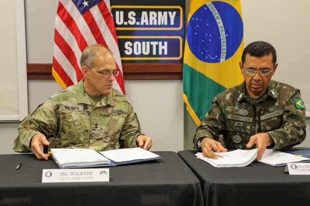 Maj. Gen. Daniel R. Walrath (left), U.S. Army South commanding general, and General de Brigada Otávio Rodrigues de Miranda Filho, 5th deputy chief of staff for the Brazilian Army, sign documents to approve agreed-to-actions and a five year plan between the two armies to conclude the U.S., Brazil army-to-army staff talks at Army South headquarters, Fort Sam Houston, Texas, Oct. 23.  The U.S. Army Staff Talks Program serves as a bilateral engagement for military discussion between respective armies. This year marks the 36th time the U.S. Army and the Brazilian Army have met for staff talks, a weeklong series of meetings that is instrumental in enhancing interoperability and cooperation between the two partners.