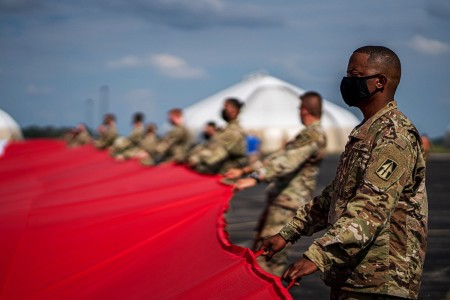 Indiana Guardsmen, donned in masks, came together to hold up a football field sized flag at the Shelbyville Aviation Flight Facility, Ind., Aug. 13, 2020.