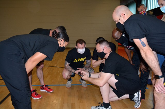 Lt. Col. Chad Flick (center), a physical therapist and the chief of the department of rehabilitation services at Landstuhl Regional Medical Center, demonstrates a fitness app during a physical readiness training leadership course.