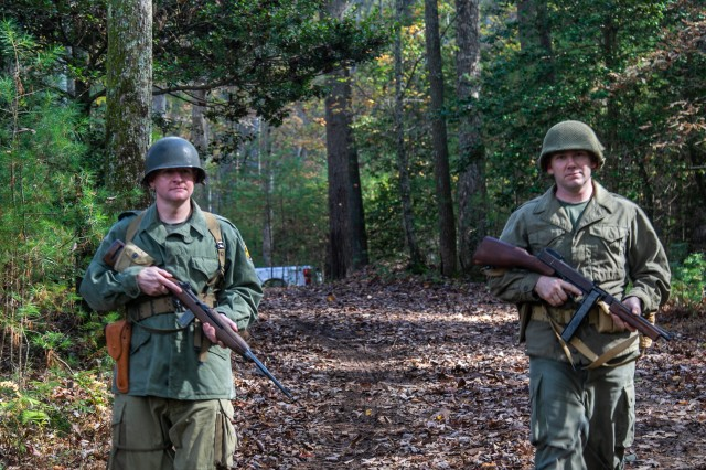 U.S. Army Maj. Thomas Bruneau, brigade intelligence officer, 1st Brigade Combat Team, 101st Airborne Division, left, and U.S. Army Maj. Trent Talley, brigade operations officer, 1st Brigade Combat Team, 101st Airborne Division, right, walk in the woods of Dahlonega, Georgia heading to receive the brigade's leaders and initiate the start of Bastogne Forge with a 26-hour tactical training event Oct. 27 in Dahlonega, Ga., during the brigade senior leader professional development exercise. The Bastogne Forge exercise took the leadership within 1BCT, 101st Abn Div. on a five day leader development exercise to strengthen bonds through shared hardship and gain a greater understanding of their unit history.