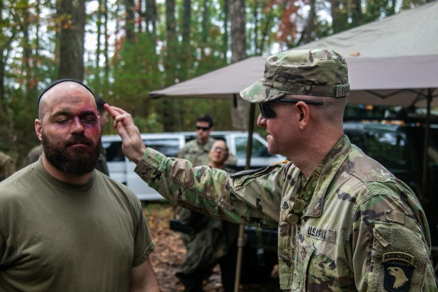 U.S. Army Maj. Thomas Bruneau, brigade intelligence officer, 1st Brigade Combat Team, 101st Airborne Division, right, carefully puts makeup on 1st Lt. Evan Shields, brigade intelligence collection officer, 1st Brigade Combat Team, 101st Airborne Division, left, as he prepares to get into character as part of the opposing forces prior to the 26-hour tactical scenario portion of Bastogne Forge Oct. 27 in Dahlonega, Ga., during the brigade senior leader professional development exercise. The brigade intelligence staff created the enemy opposing forces scenario based upon a WWII theme paying homage to the brigade's illustrious history.