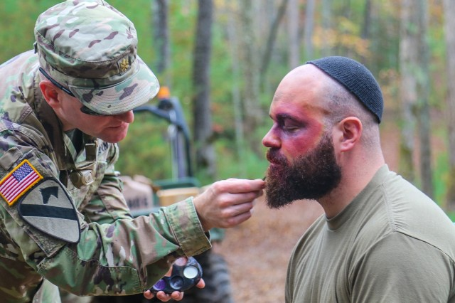 U.S. Army Maj. Thomas Bruneau, brigade intelligence officer, 1st Brigade Combat Team, 101st Airborne Division, left, carefully puts makeup on 1st Lt. Evan Shields, brigade intelligence collection officer, 1st Brigade Combat Team, 101st Airborne Division, right, as he prepares to get into character as part of the opposing forces prior to the 26-hour tactical scenario portion of Bastogne Forge Oct. 27 in Dahlonega, Ga. during the brigade senior leader professional development exercise. The brigade intelligence staff created the enemy opposing forces scenario based upon a WWII theme paying homage to the brigade's illustrious history.